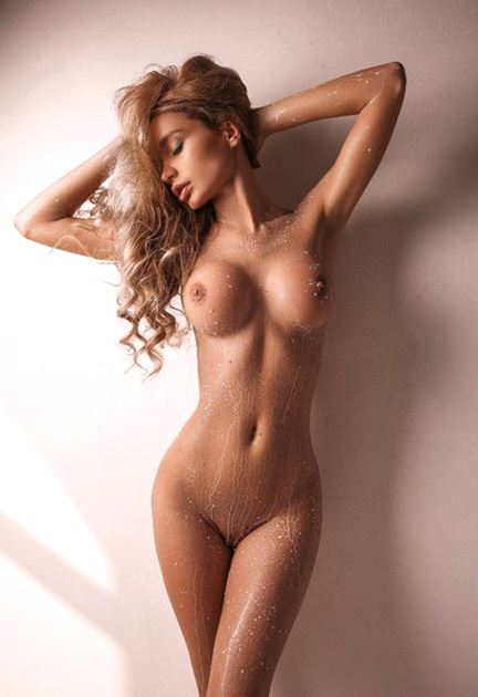 naked dreamy babe standing by wall