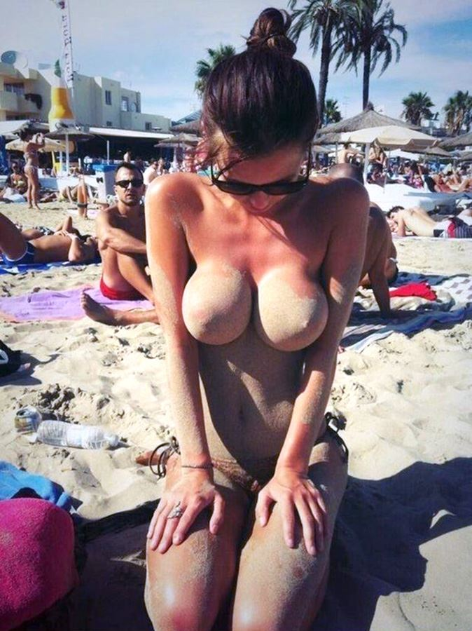 girl at the beach with sand on boobs