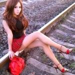 innocent looking sexy brunette sitting on trailroad