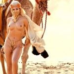 naked arabian woman standing next to camel