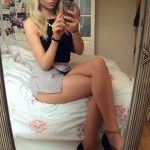 sexy blonde makes pic of herself sitting on bed